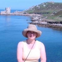 Leslie Skibinski wearing a hat with coastline of England and a castle in the background.