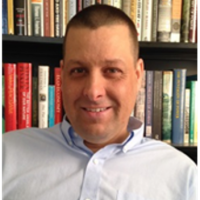 Greg Dietl with a bookshelf in the background.