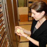 Jann holding fossil specimen, standing in front of open collections cabinet