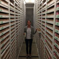 Christine in hallway lined with museum drawers full of microfossil specimens