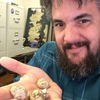 Jim Parham in his office holding bivalve specimens in his hand.