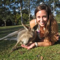 Allison Shafer lying on grass next to a small donkey.
